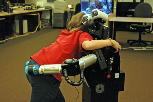 A study participant and Robovie share a hug, one of the social interactions in the UW experiment.