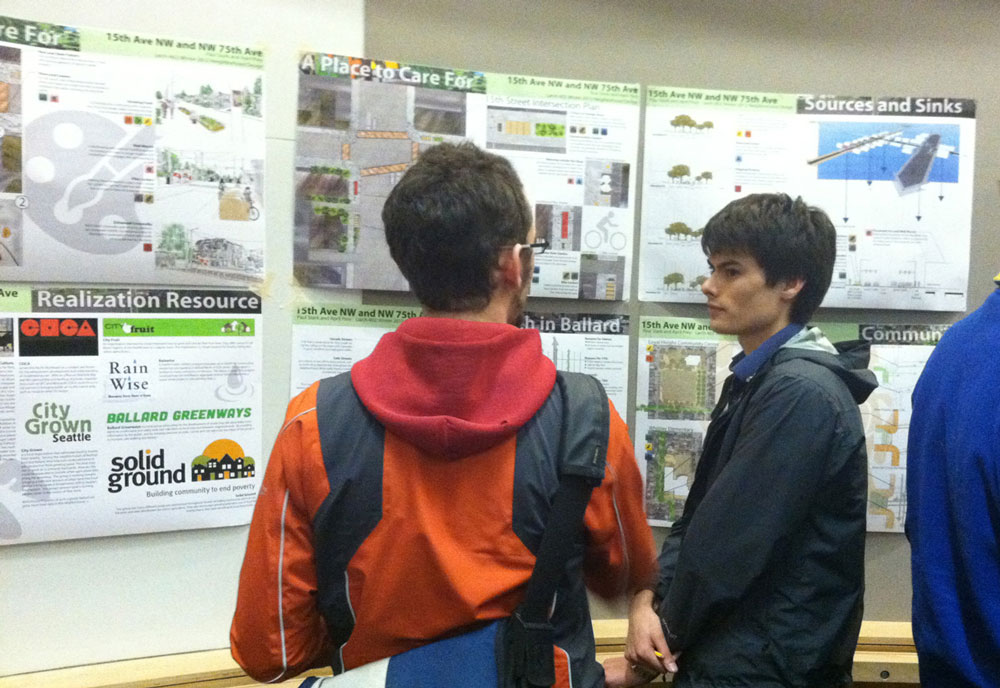 At a Ballard District Council meeting in mid-March, student Paul Stark listens to an attendee. He is standing in front of designs he and another student, April Prey, developed for the Northeast 75th Street Rapid Ride stop area.