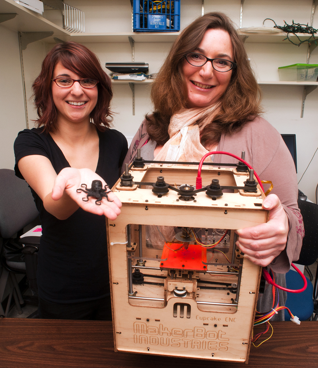 Beth Kolko and master's student Alexis Hope together conceived of Hackademia. They hold a student-built 3-D printer and an octopus that was created with it.