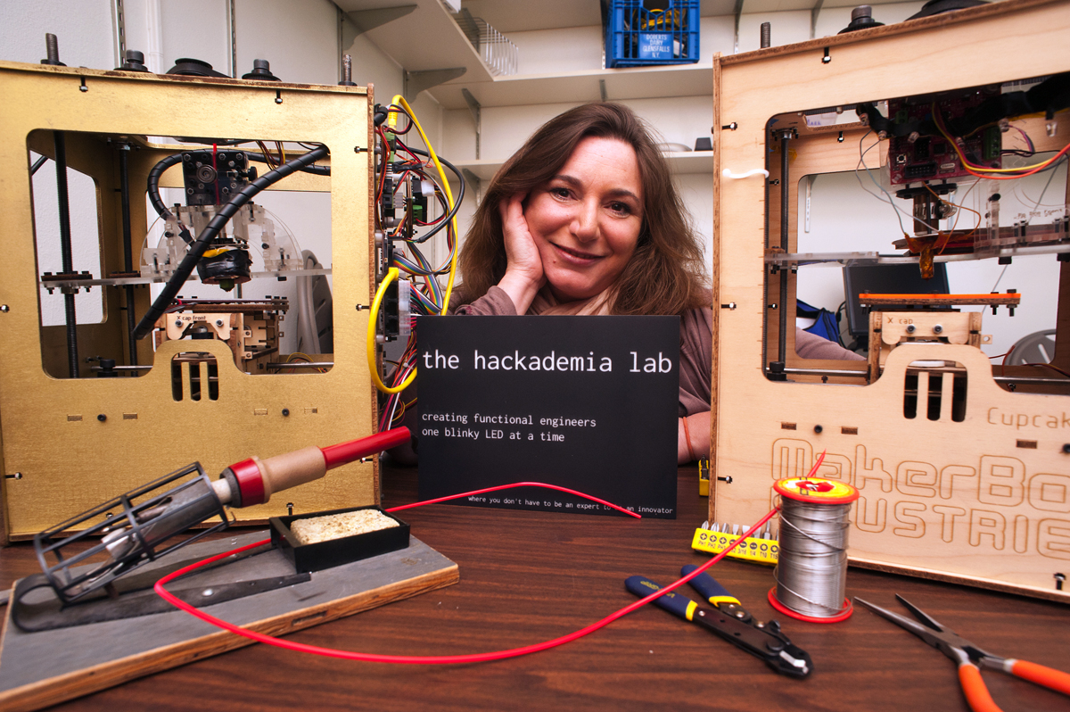 Beth Kolko with two 3-D printers built by past classes. She made the course sign herself, and came up with the class motto as she was programming the design.