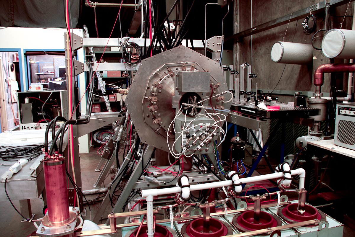 The lab equipment includes a small system that measures plasma for electronics applications, attached to a larger tank containing plasma for energy research.