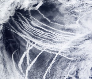 A satellite image shows white streaks stretching across the ocean. The streaks are ship trails, clouds the form around pollution emitted from ships into the air.