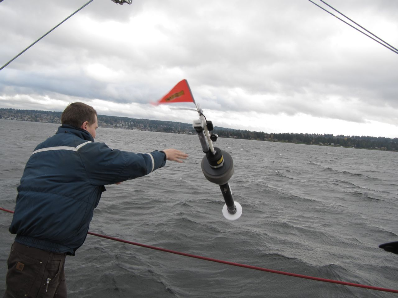 a photograph of the scientist throwing a long, tubular buoy with a red flag on top from a ship into the water.