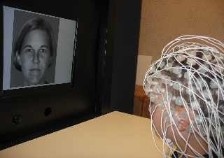 child wearing EEG electrodes looks at a face