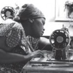 Garment worker using sewing machine