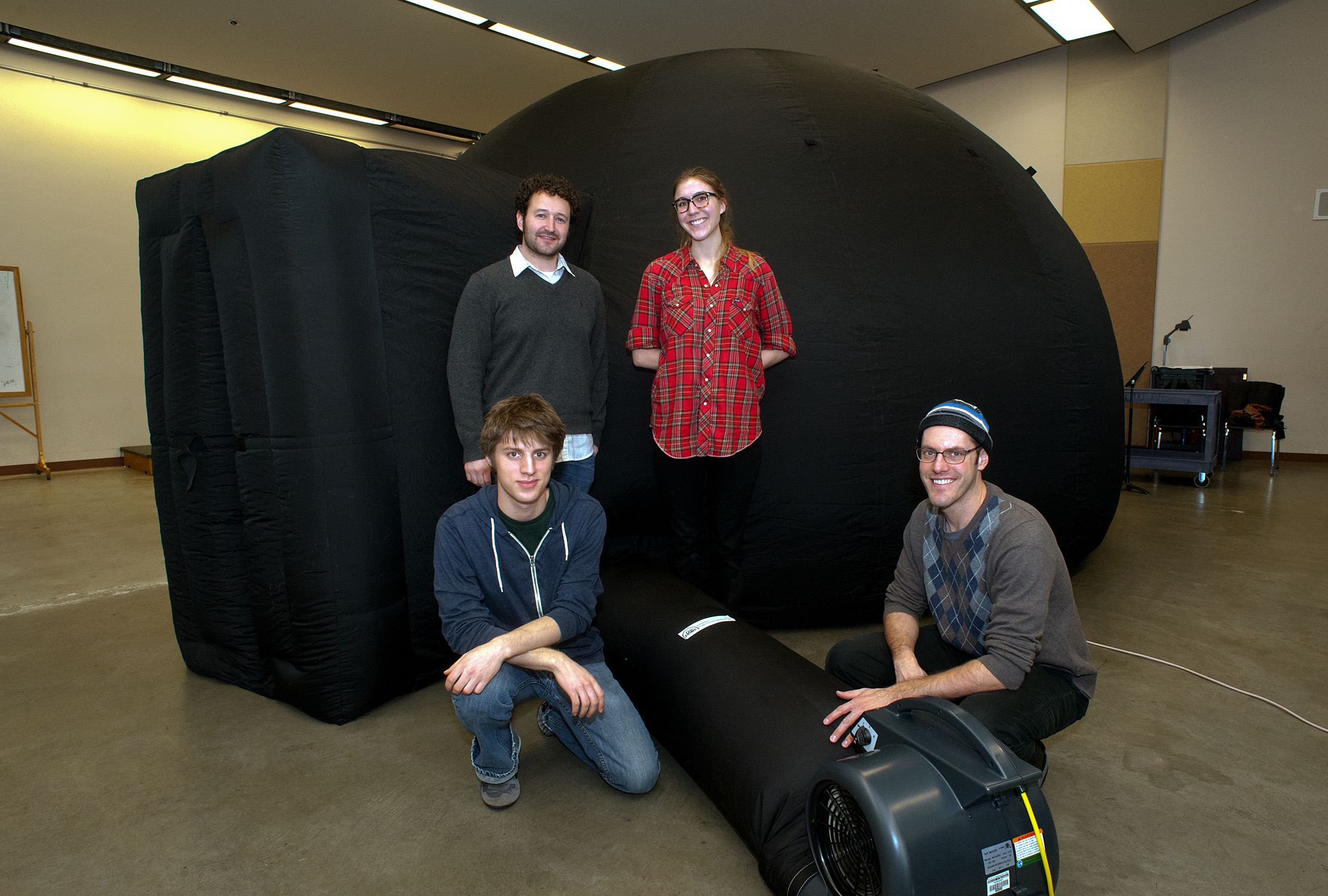 The UW astronomy department's new portable planetarium may look like an inflated igloo, but it is actually an innovative teaching tool, and will enable young students to create their own planetarium shows. Team members from left are Justin Gailey, Phil Rosenfeld, Nell Byler and Oliver Fraser.