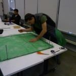 Student stips fiber from green rectangle of landscape matting on top a table
