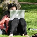 A student looks at a computer on the UW Quad.