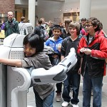 A student gets a hug from a robot.