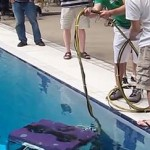 Two operators stand on deck operating an underwater robot in a swimming pool