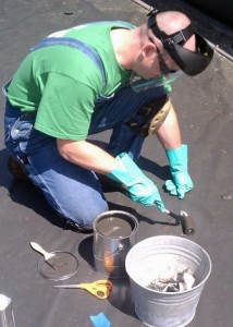 Man kneeling down using a roller to apply patching compound