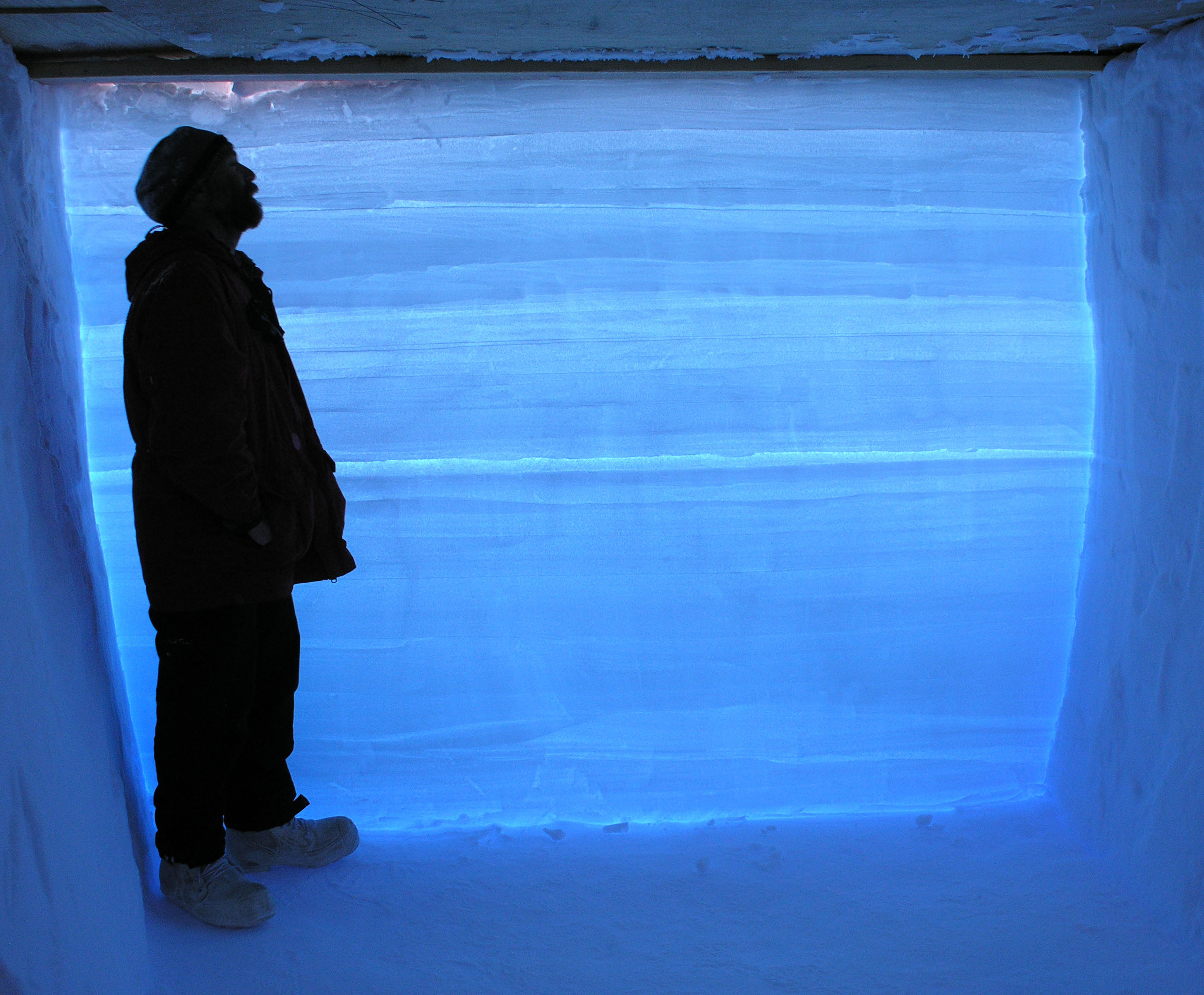 A researcher stands in a snow pit next to an Antarctic ice core.