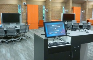 An instructor's station is ready for use in an active-learning classroom. Each table is fully wired and has space for nine students.