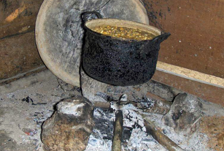 A crude cook stove over open flame.