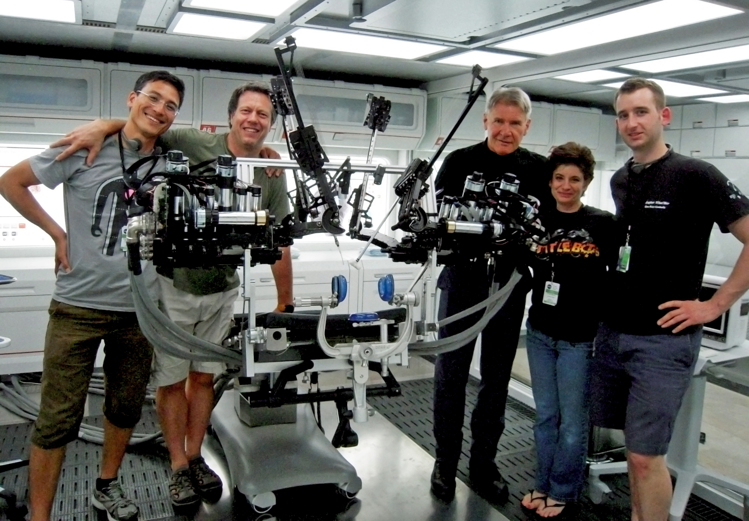 On the movie set with the University of Washington's Raven II surgical robot. From left to right: Hawkeye King, director Gavin Hood, Harrison Ford, robotics expert Joanne Pransky and Lee White.