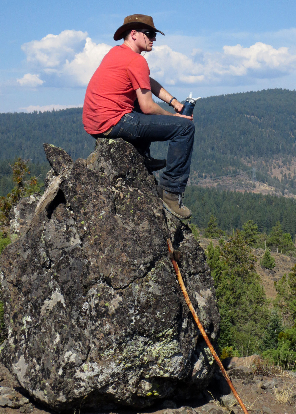 Students sits on top of 10-foot boulder