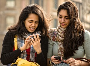 Two friends check their smartphones.