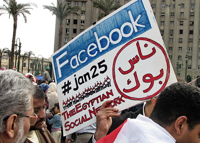 Protestors hold up a Facebook placard in Tahrir Square