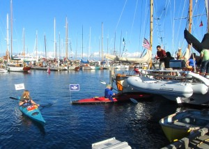 Two kayakers visit boaters, handout packages with adapters