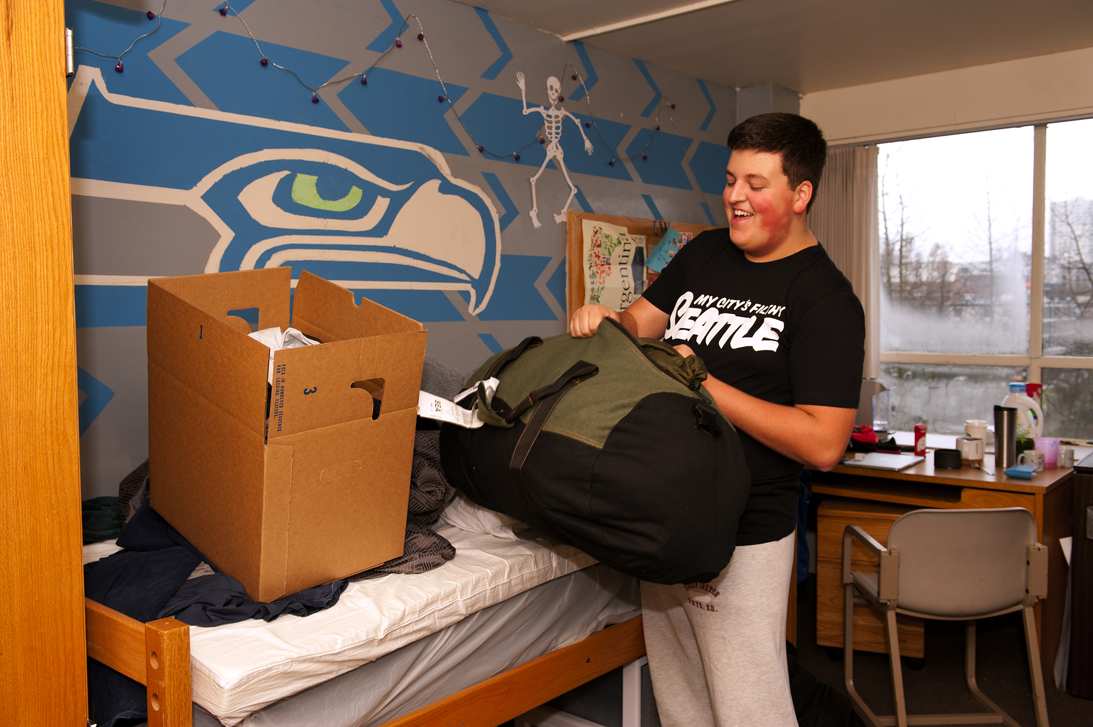 Student Ben Ferrara packs up his room in preparation for moving to the new Lander Hall. Since the building is soon to be closed, he and roommate Evan McAuley were allowed to paint a Seahawks logo on their wall.