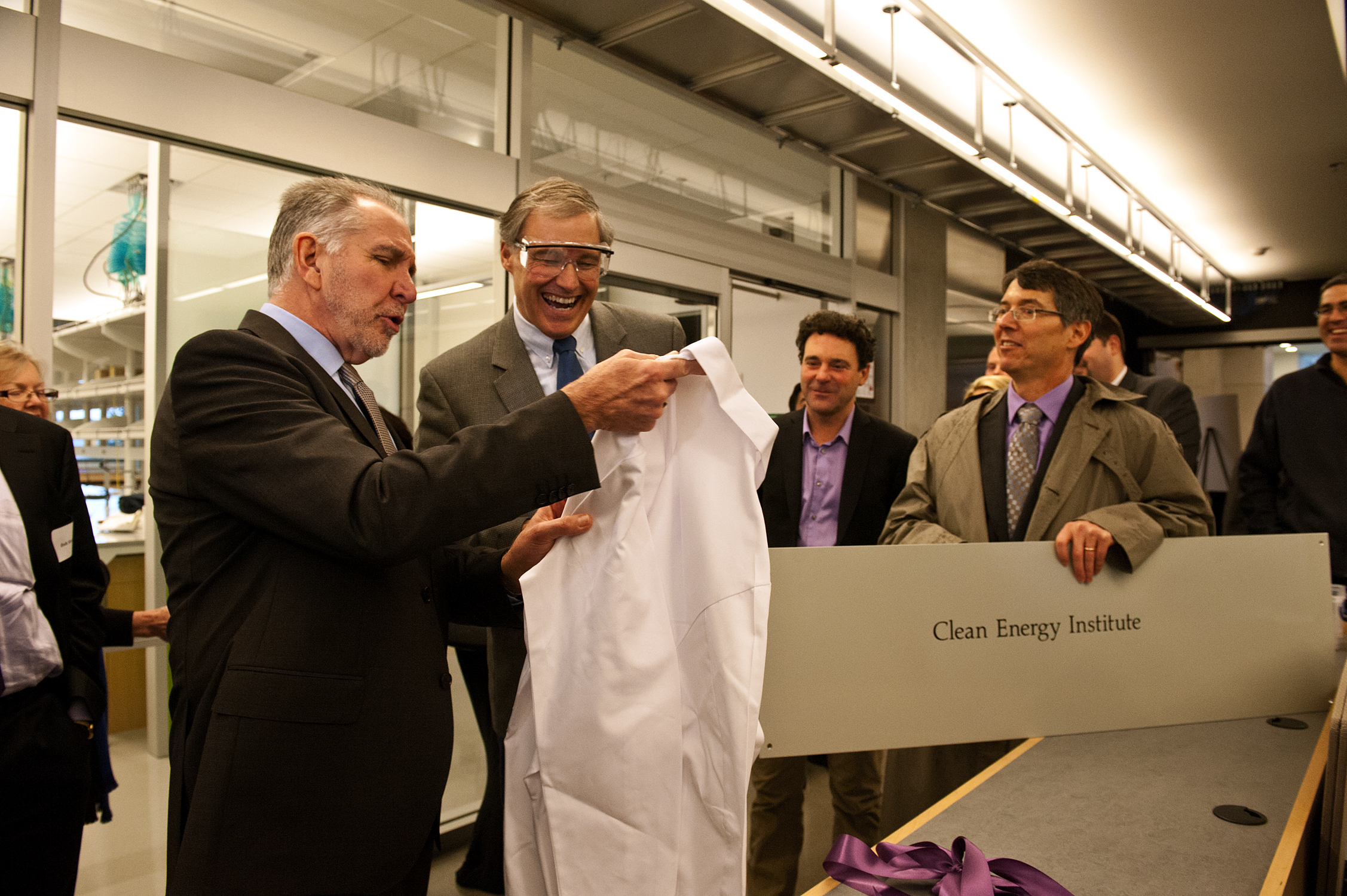 UW President Michael Young presents Gov. Jay Inslee with a lab coat at the launch of the Clean Energy Institute on Dec. 12.
