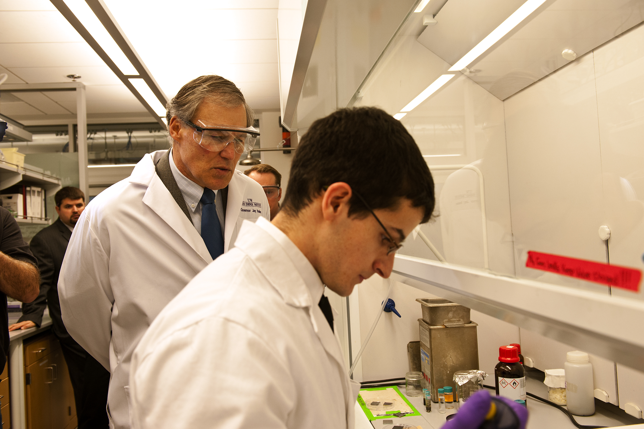 Gov. Jay Inslee watches as Wes Williamson, a UW chemical engineering graduate student, runs a demonstration in a lab.