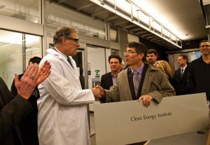 Gov. Jay Inslee (center) shakes hands with Dan Schwartz, director of the new Clean Energy Institute, with UW President Michael Young (left).