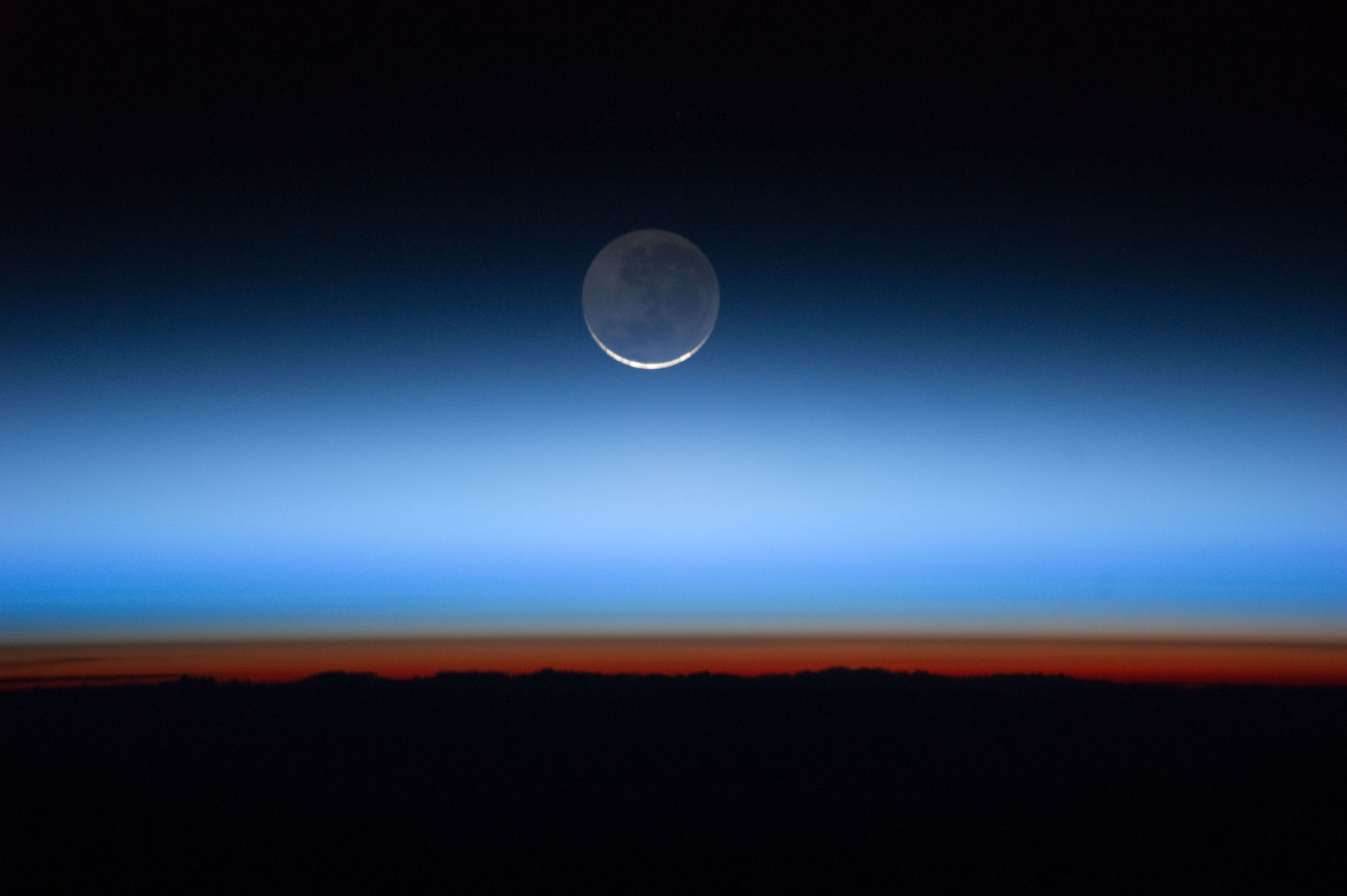 The sun is just below the horizon in this photo and creates an orange-red glow above the Earth's surface, which is the troposphere, or lowest layer of the atmosphere. The tropopause is the brown line along the upper edge of the troposphere. Above both are the stratosphere, higher atmospheric layers, and the blackness of space.