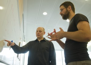 Population geneticists Joshua Akey (left) and Benjamin Vernot (right) discuss models of human evolution.