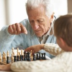 elderly man teaches chess