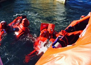 Two simmers in survival suits in water trying to climb into opening of covered life raft