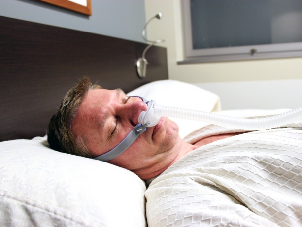 a man sleeps in a bed with a CPAP machine