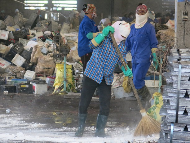 a worker sweeps the floor of a Vietnam battery-recycling factory