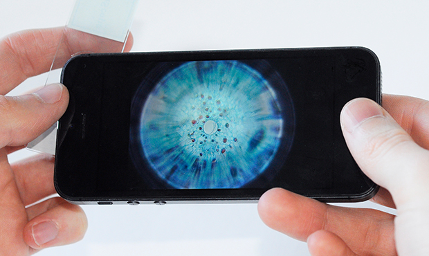 A magnified image is shown on an iPhone screen.