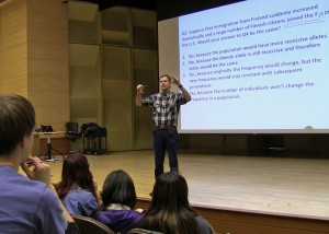 Man stands on stage in front of class, behind him is screen with questons