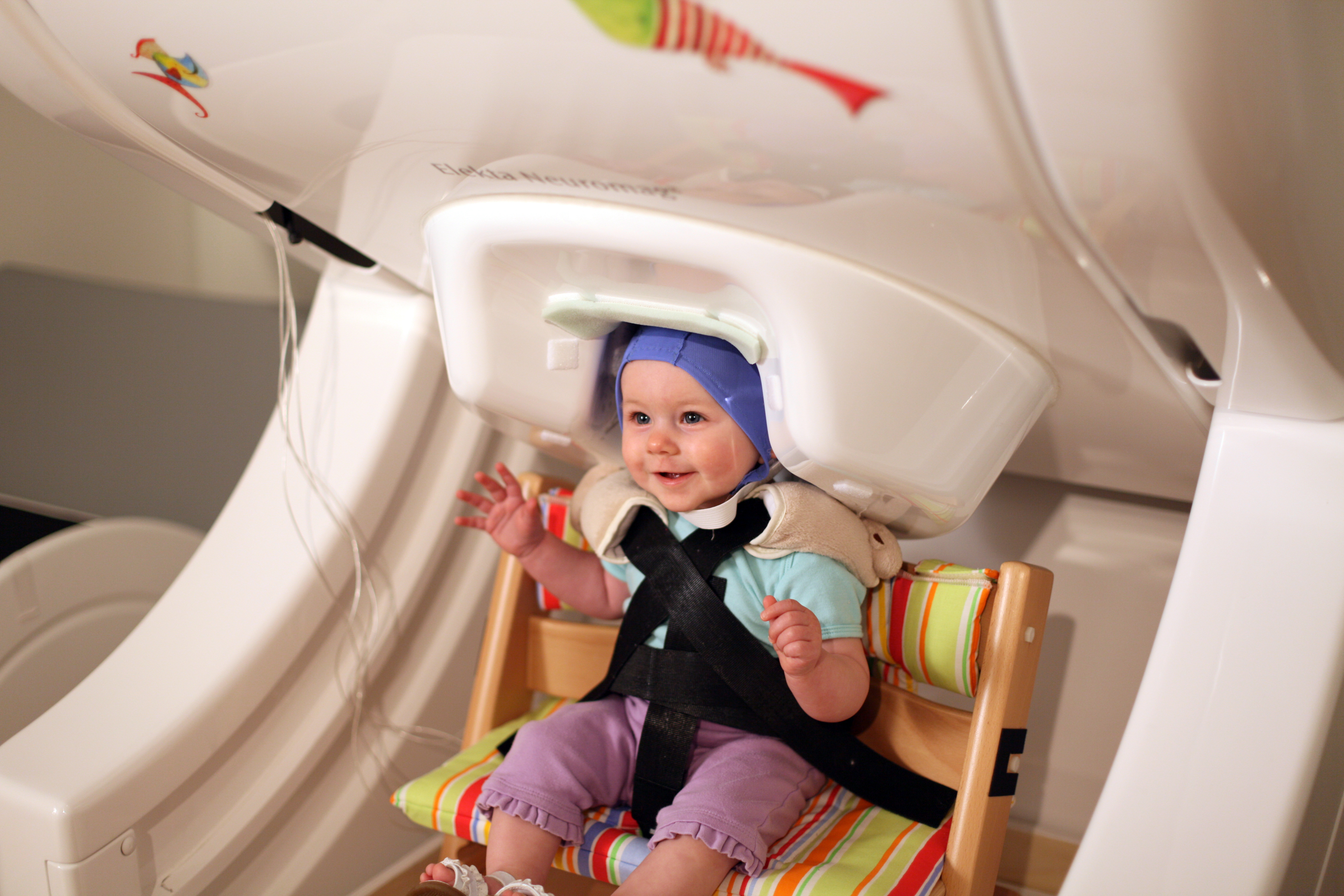 "A year-old baby sits in a brain scanner, called magnetoencephalography -- a noninvasive approach to measuring brain activity. The baby listens to speech sounds like ""da"" and ""ta"" played over headphones while researchers record her brain responses."