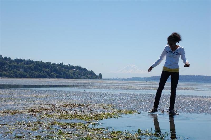 Girl on the shoreline with mountain in background.