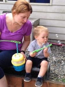 Jen Zaffram with a child blowing bubbles.