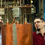UW physicists Leslie Rosenberg (left) and Gray Rybka examine the Axion Dark Matter Experiment detector package.