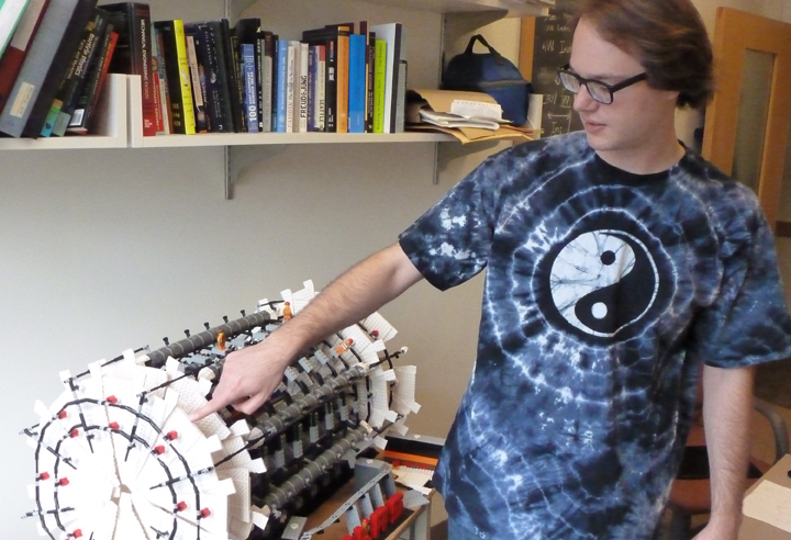 UW physics graduate student Nikola Whallon shows off a Legos version of the Atlas detector.