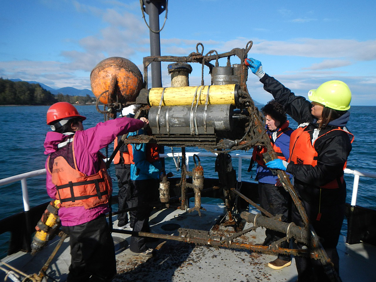 students clean instrument on boat deck