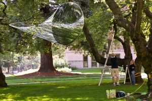 Artist Alyson Piskorowski, right, looks on as colleagues help her install her untitled work in the Quad outside Savery Hall. Piskorowski, who earned an MFA from the UW in sculpture and public art, is one of several UW alumni showing art during the Mad Campus art exhibition.