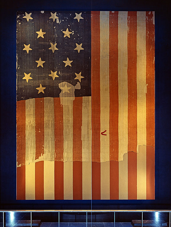 "The flag that inspired Francis Scott Key to write what would become ""The Star Spangled Banner,"" shown on display at the Smithsonian's National Museum of History and Technology, around 1964. Many pieces were cut off the flag and given away as souvenirs early during its history. A linen backing, attached in 1914, shows the original extent of the flag."