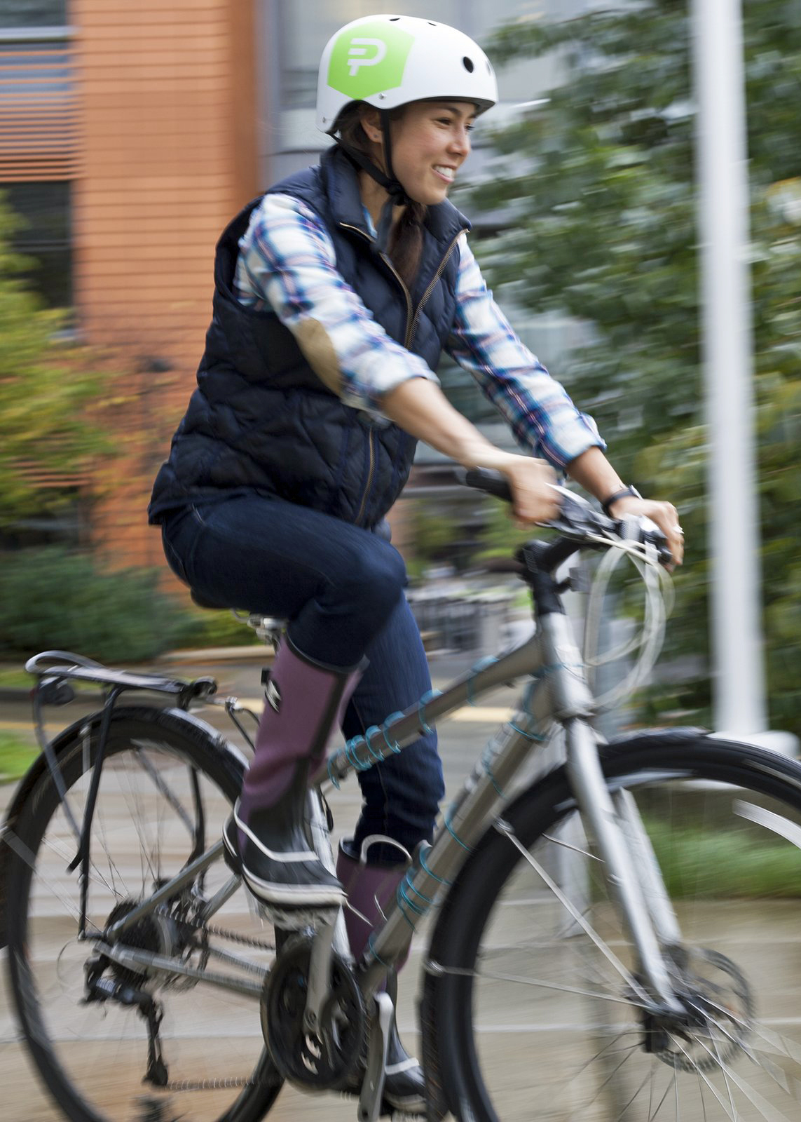 Woman rides bicycle across campus