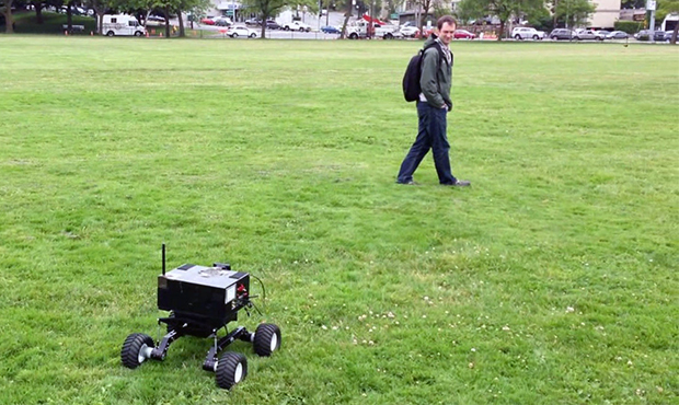 A robot equipped with a camera follows a researcher by tracking him as he walks.