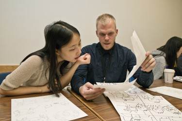 Undergraduate students Xiangyi (Anne) Zheng, left, and Daniel Aldridge give feedback on each other's comics at a recent class.