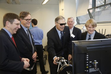 From left: UW College of Engineering Dean Michael Bragg, Department of Mechanical Engineering chair Per Reinhall, Boeing engineer Jim Buttrick and UW graduate student Parker Owen walk Gov. Jay Inslee through a robotics demonstration at the center's opening event.