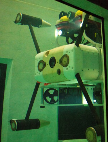The Millennium Falcon robot maneuvers underwater in a testing tank on campus. The monitoring instruments (white box in the middle) are guided by the robot's thrusters toward a docking station on the bottom of the tank. Researchers controlled the machine from above.