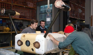 From left to right: UW researchers Ben Rush, Nick Michel-Hart, James Joslin and Paul Gibbs prepare to test the monitoring device underwater in a tank on campus.