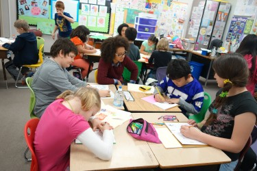 Alexandra Lynn Zepeda, middle, works with students at Forks Elementary on a literacy project.